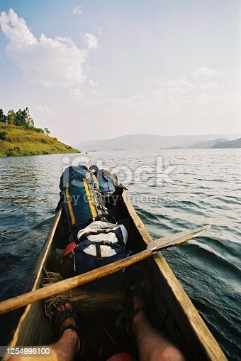 istock Dugout canoe feet oar backpacks and travelling feet on an African Lake 1254996100