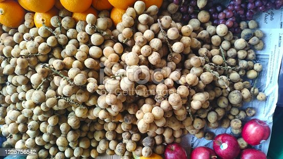 Duku fruit for sale at street market in vietnam. Duku fruit. Tropical fruit from southeast asia with sweet taste and bitter fruit seeds. After 3 days the skin will turn black