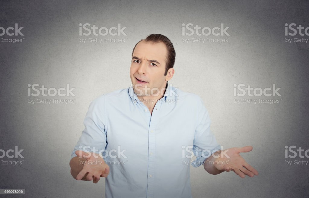 dumb clueless funny looking young man, arms out asking what's the problem stock photo