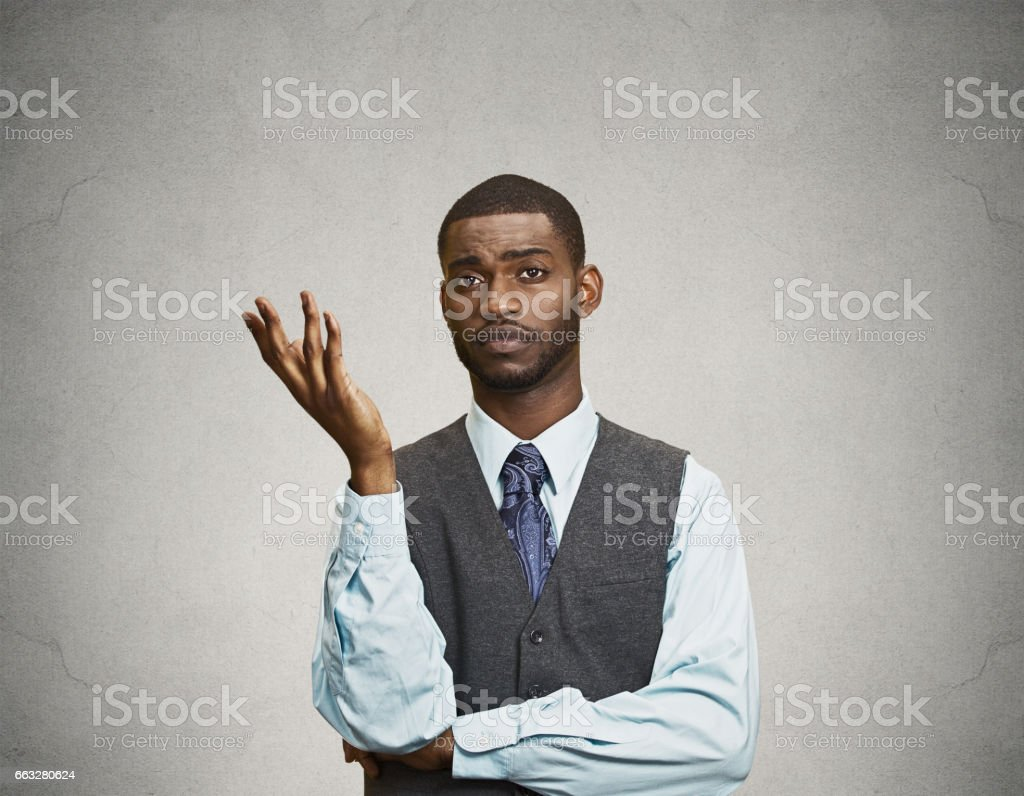 dumb clueless young executive man, arm out asking why what problem so who cares stock photo