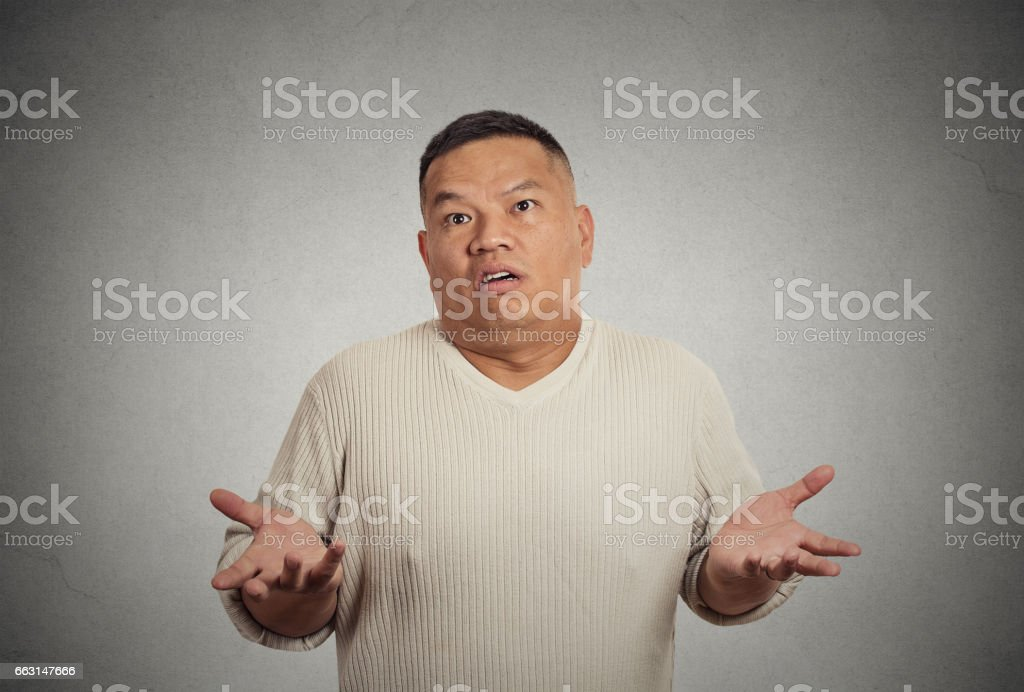 dumb clueless young man arms out asking why what's problem who cares stock photo