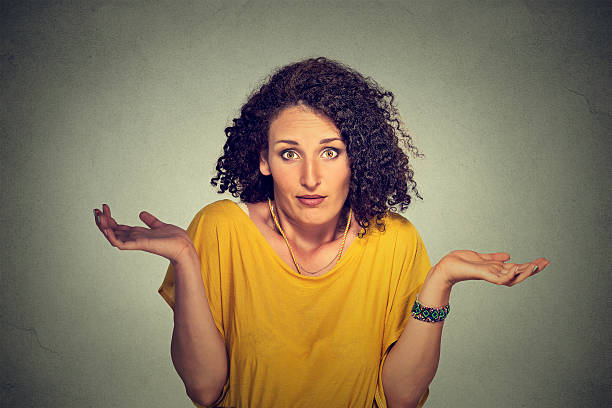 dumb looking woman arms out shrugs shoulders - stupidblonde stock pictures, royalty-free photos & images