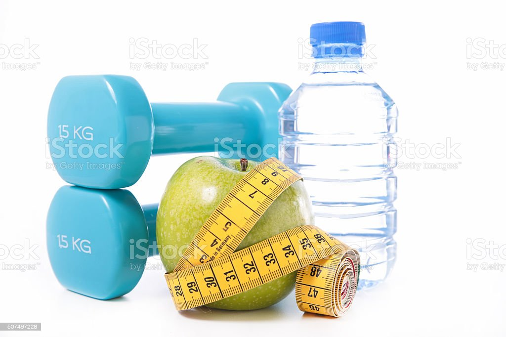 dumbbell and apple with measuring tape stock photo