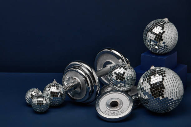 Dumbbell and mirror balls. Fitness New Year and Christmas background stock photo