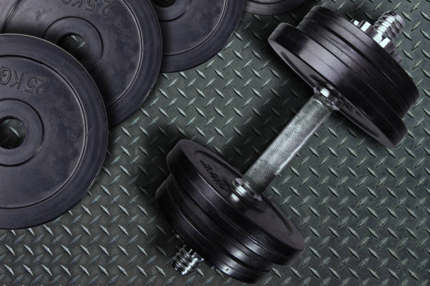 Dumbbell and weights on a wooden background. – zdjęcie