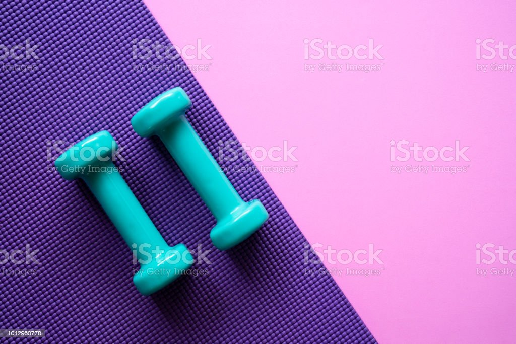 dumbbell and yoga mat on table, fitness healthy and sport concept stock photo