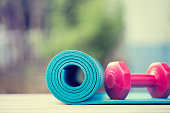 dumbbell and yoga mat on wood table