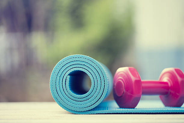 dumbbell and yoga mat on wood table stock photo