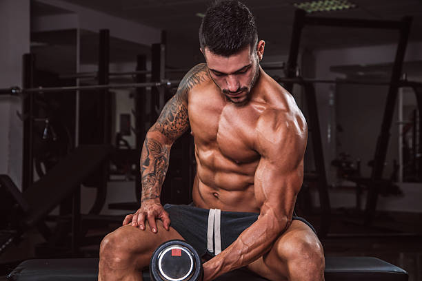 Dumbbell Bicep Curls Bodybuilder performing heavy dumbbell bicep curls. macho stock pictures, royalty-free photos & images
