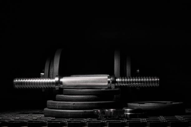 Dumbbell for strength training on a dark background. stock photo