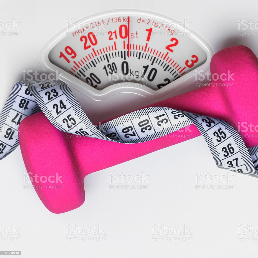 Dumbbell measuring tape on weight scale. Fitness stock photo