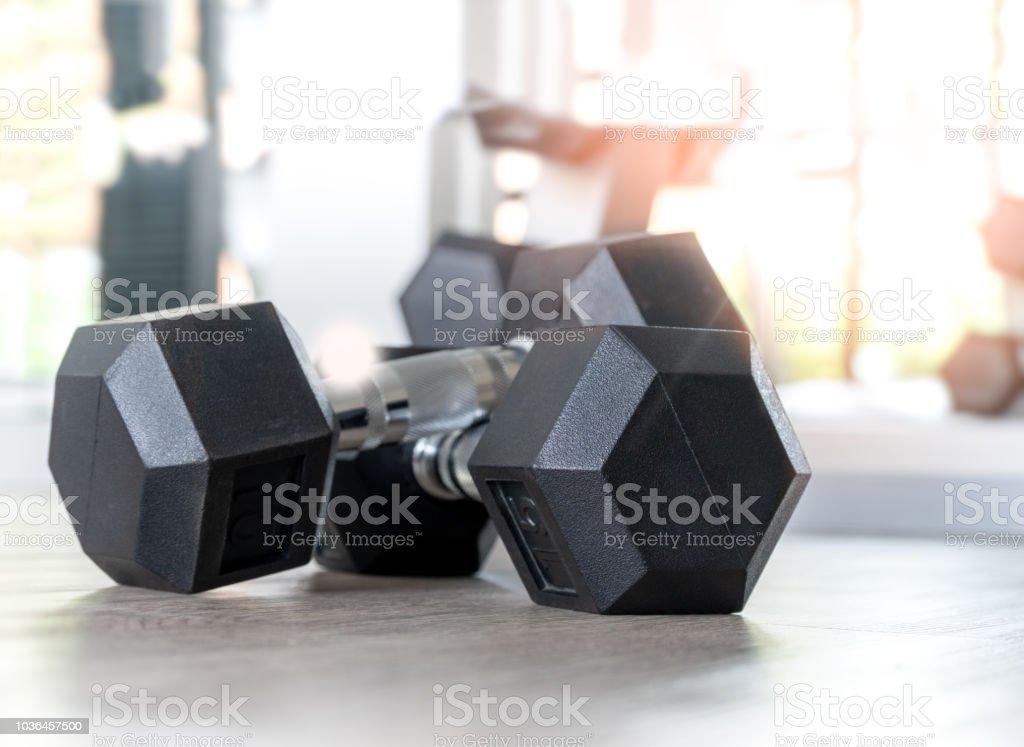 Dumbbell on the floor in fitness room. stock photo