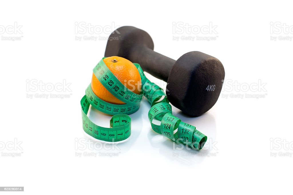 Dumbbell, orange and measuring tape on a white background. stock photo