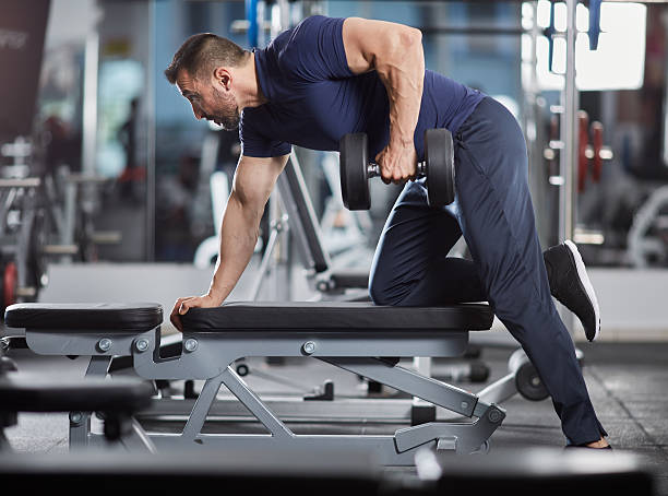 Dumbbell row in the gym Man doing dumbbell row for back workout in the gym dorsal fin stock pictures, royalty-free photos & images