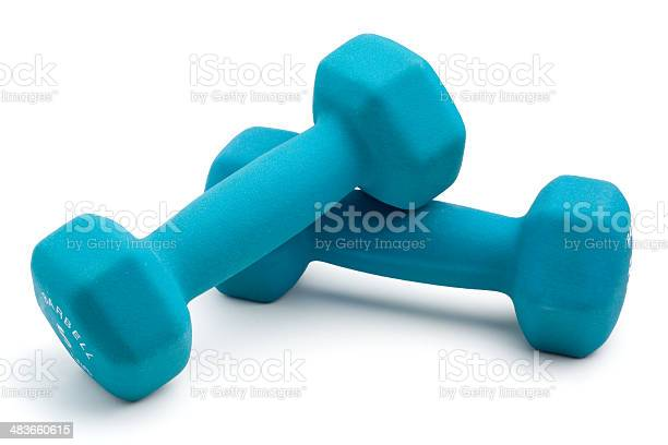Two dumbbell weights isolated on white with soft shadow.
