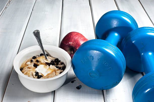 Hanteln und red apple neben Schüssel mit Joghurt – Foto