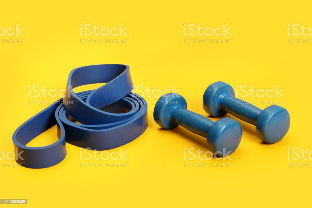 light weight dumbbells and a blue exercise resistance band on a...