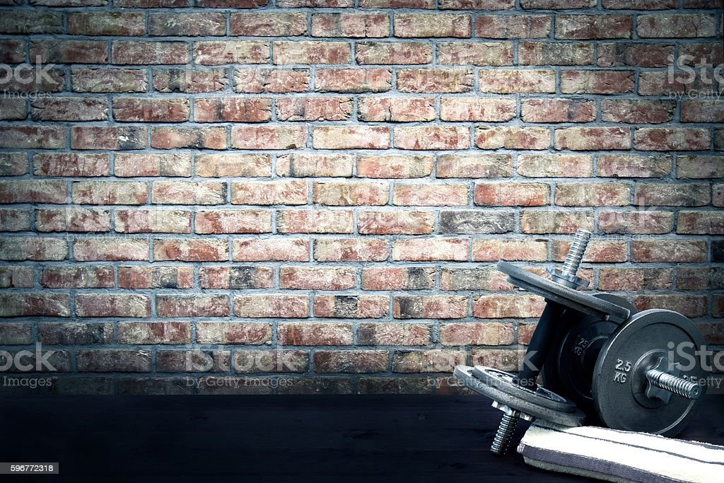 Dumbbells and towel lying on the ground in vintage stylization. stock photo