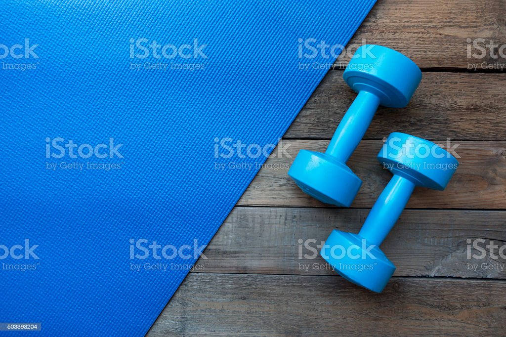 dumbbells and yoga mat on wood table