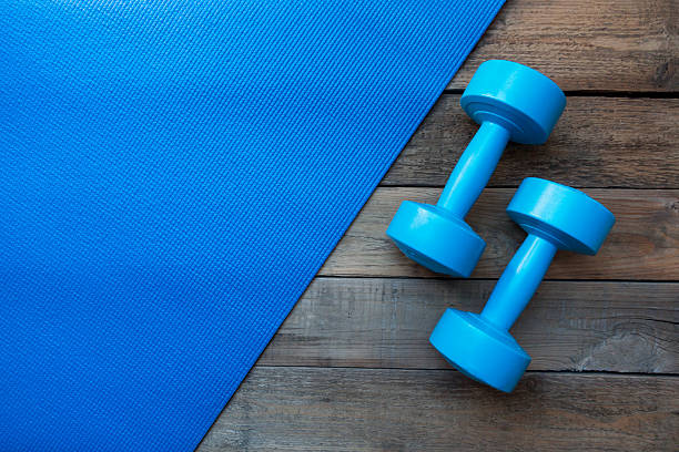 dumbbells and yoga mat on wood table stock photo