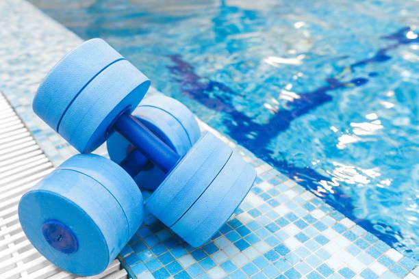 dumbbells equipment for aqua aerobics sport near swimming pool stock photo