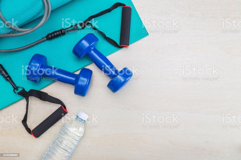 ejercicio de pesas, equipo, estera de la yoga gimnasio y botella de agua en el piso de madera limpio, sano y bien ser concepto, con espacio para texto o copia espacio foto de stock libre de derechos