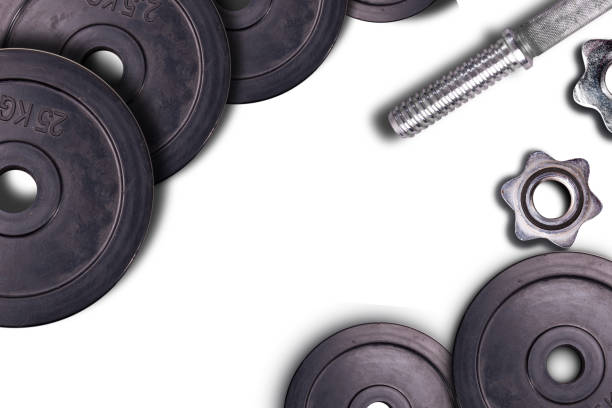 Dumbbells on carbon background. Dumbbells and weights are lying on the floor in the gym. Barbell set and gym equipment. Metal loads in the fitness club. – zdjęcie