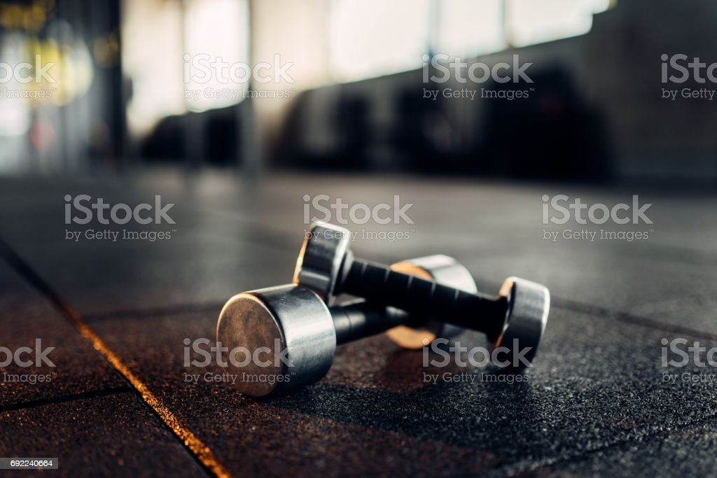 Dumbbells on rubber floor closeup, fitness club stock photo
