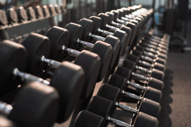 dumbbells on stand in gym - dumbbell stock pictures, royalty-free photos & images