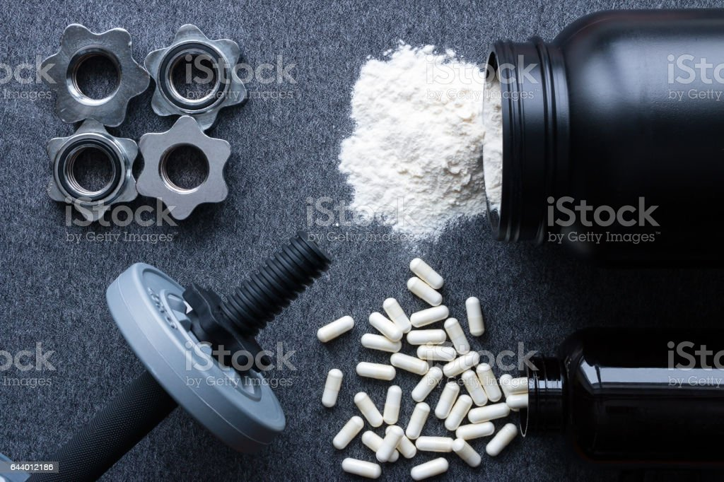 dumbbells, protein and amino acids on a gray background – Foto