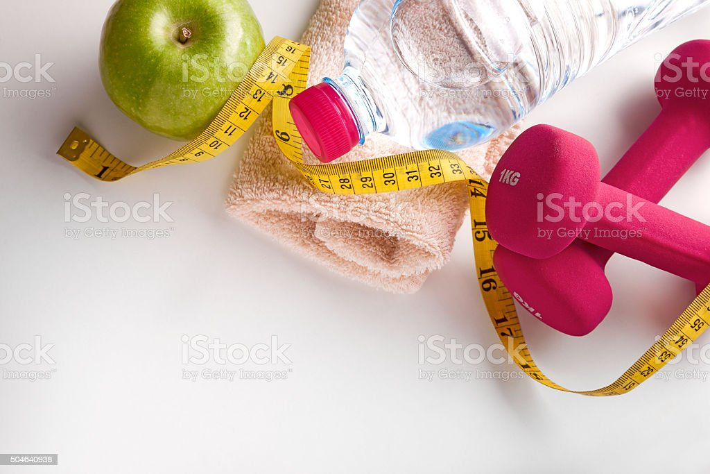 Dumbbells with apple bottle and tape measure and towel top stock photo