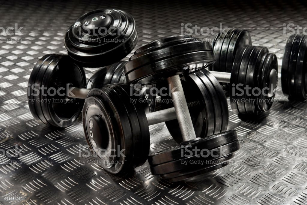 dumbbells with black discs weighting on the floor stock photo