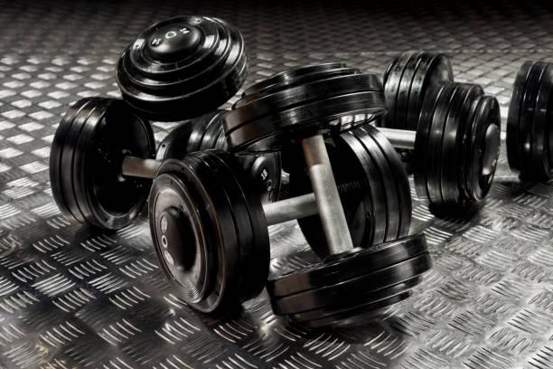 dumbbells with black discs weighting on the floor stock photo