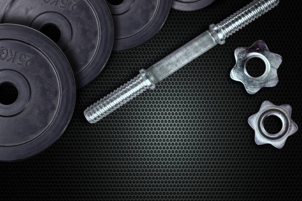 Dumbells and weights on a carbon background. Fastening screws and barbells. – zdjęcie