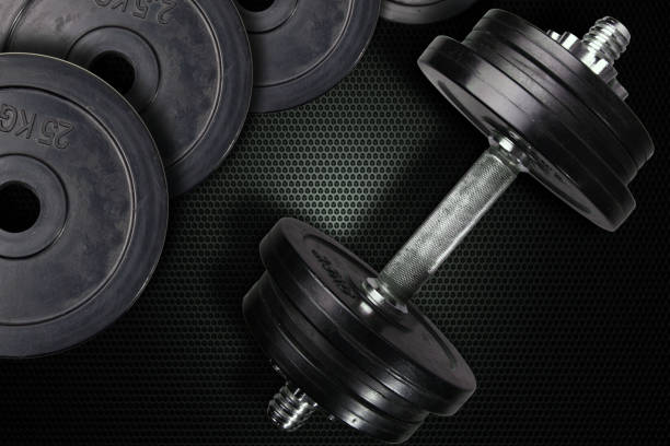 Dumbells and weights on a carbon background. – zdjęcie