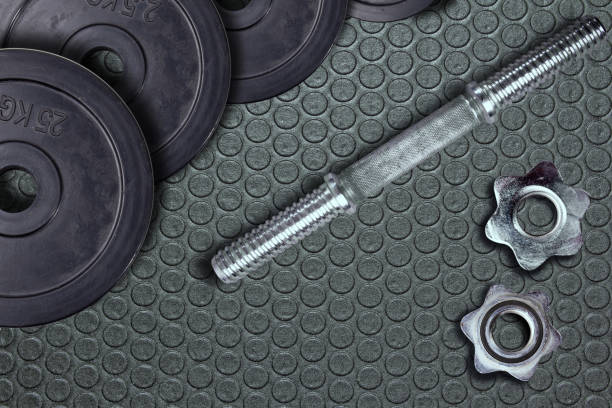 Dumbells and weights on the exercise mat. Fastening screws and barbells. – zdjęcie
