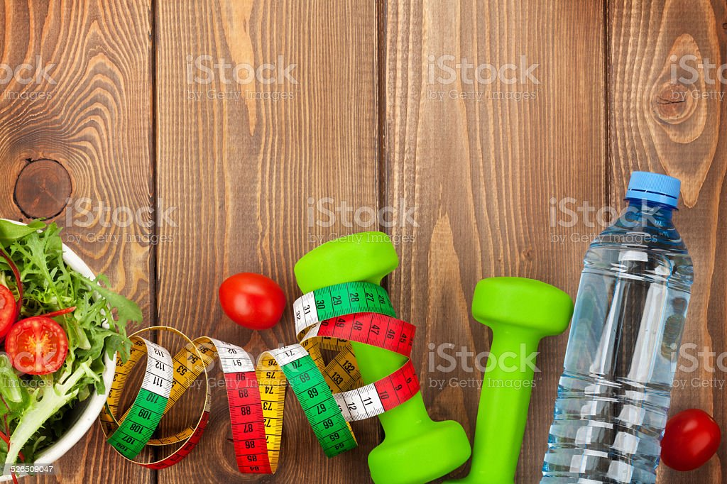 Dumbells, tape measure and healthy food over wooden background....