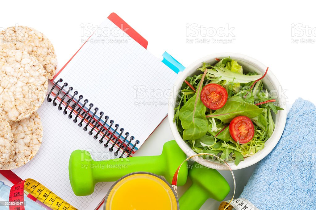 Dumbells, tape measure, healthy food and notepad for copy space. stock photo