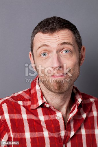 satisfaction and smile concept - childish middle age man with checked shirt apologizing to smile like an idiot expressing satisfaction or fool mistake