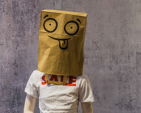 dummy wearing a funny paper bag on its head and a t-shirt with Sale on it, shopping discount concept