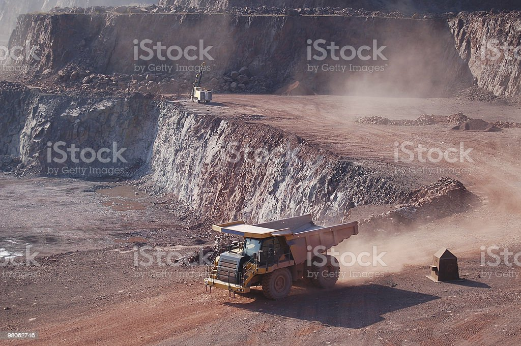 Dump truck driving through mining quarry royalty-free stock photo
