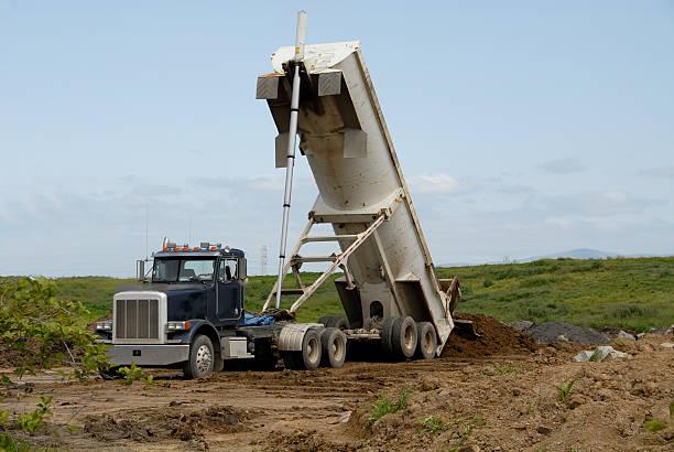 Dump truck dumping dirt into a field stock photo
