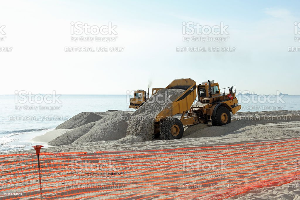 Dump Truck Dumping Sand on the Beach stock photo