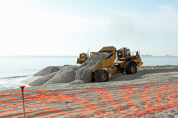 Dump Truck Dumping Sand on the Beach Fort Lauderdale, FL, USA - March 3, 2016: Piles of sand dumped on the beach shore replenish and widen. eroded stock pictures, royalty-free photos & images