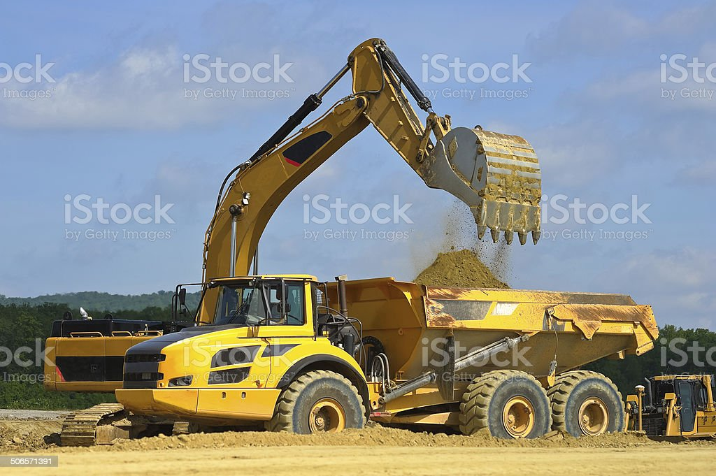 Dump truck is loaded by excavator royalty-free stock photo