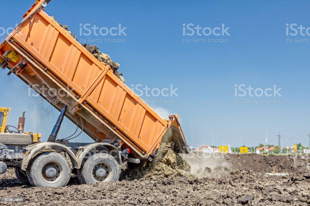 Dump truck is unloading soil stock photo