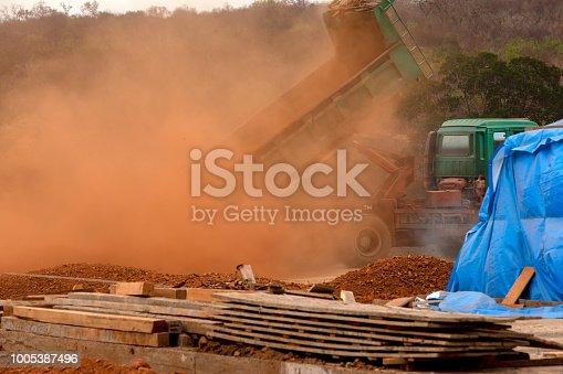 istock dump truck unloading dirt at construction site 1005387496