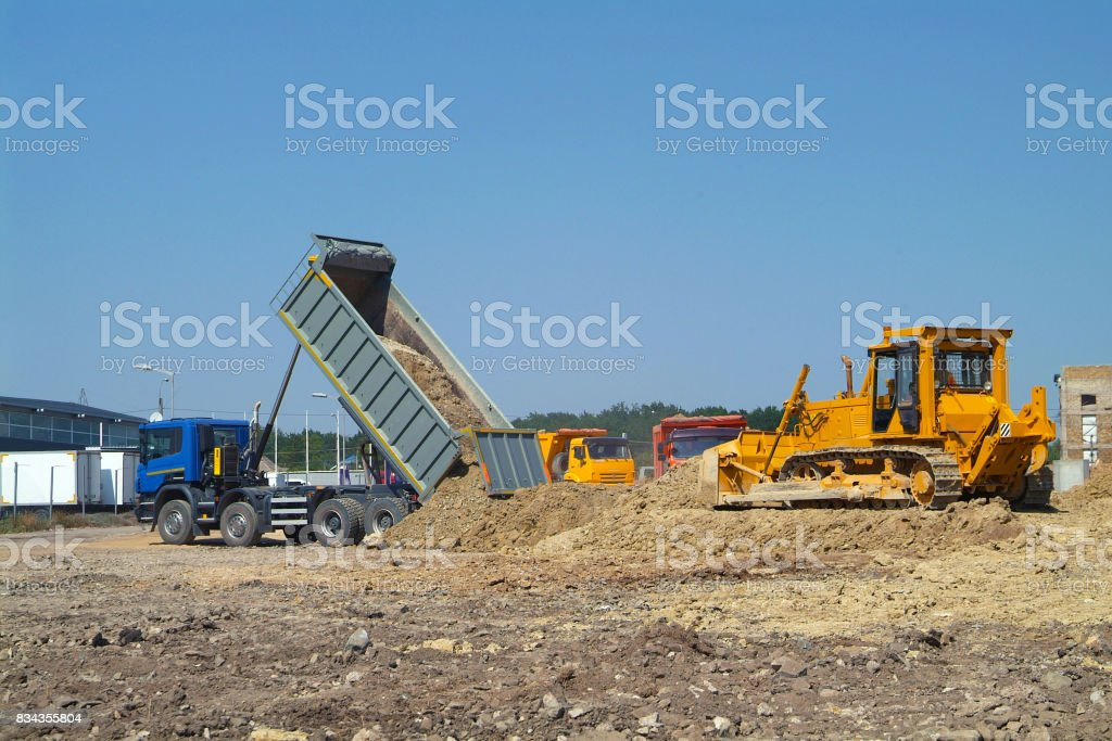 Dump Truck Unloading Soil And Bulldozer Move This Earth On Construction Site Royalty Free Stock