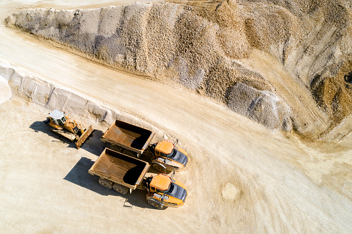 Aerial view of two dump trucks and a bulldozer in a quarry.