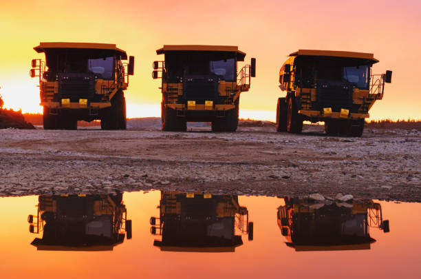 Dump trucks at a construction site at sunset stock photo